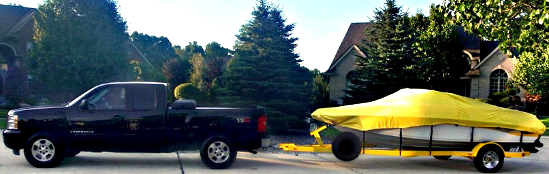 boat with a yellow cover being pulled behind a black truck