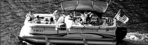 black and white photo of a pontoon boat on lake