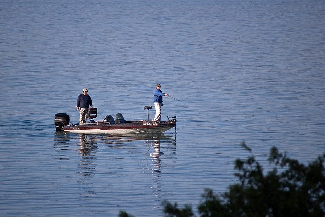 two fishermen on a boat enjoying the lake on a nice day