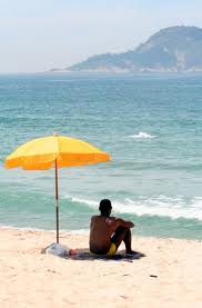 man sitting under a beach umbrella beside the water