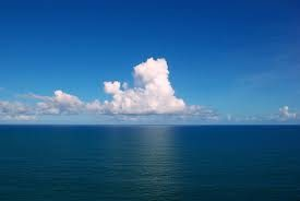 beautiful picture of a deep blue sea with bright blue sky and white puffy clouds