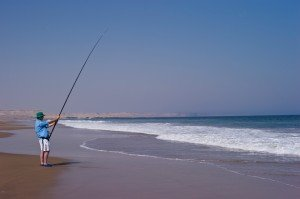 man fishing with a long fishing rod from a beach