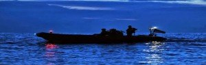 Navy inflatable boat on water at night