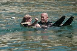 man and little girl in water learning to water ski