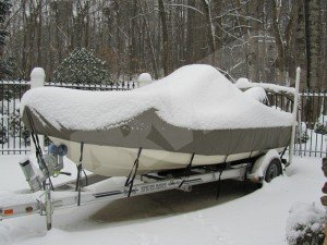 boat cover on boat that is covered in snow